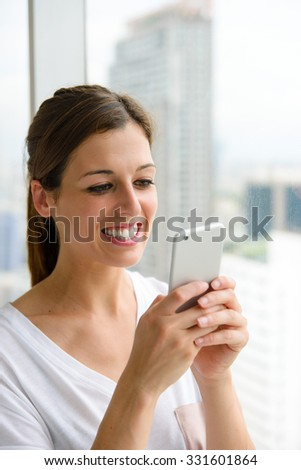 Woman texting on smartphone at home near the window.