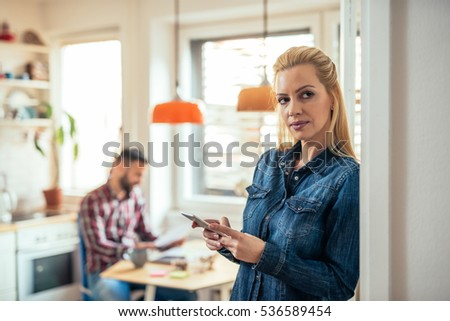 Woman texting on the phone at home.