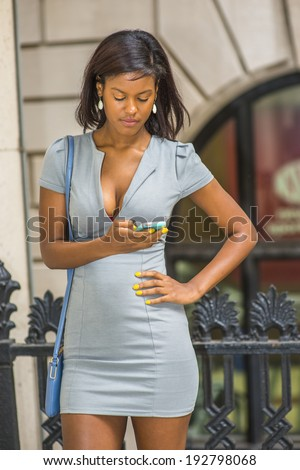 Woman texting outside. Wearing a gray business dress, drop earrings, carrying a shoulder small bag, a young beautiful black businesswoman is looking down, reading messages on her cell phone.  - stock photo
