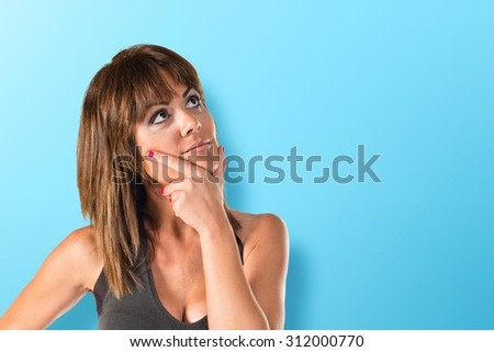 Woman thinking and looking up over colorful background - stock photo