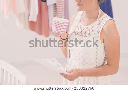 Woman thinking over design with cup of tea