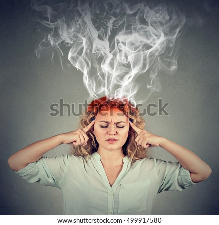 Woman thinks very intensely having headache isolated on gray wall background