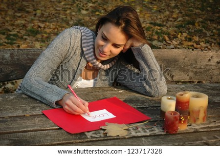 woman thoughtfully smiling, leaning on the arm, writing word LOVE on white and red paper on wooden table with candles - stock photo