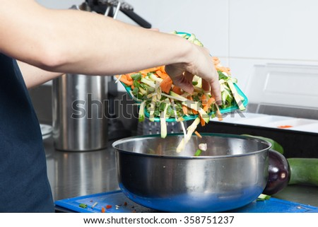 Woman throw some vegetables in a bowl