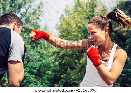 Woman throwing a punch to man on taebo training - stock photo