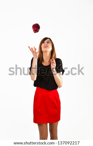 Woman throwing an apple upwards. White background.