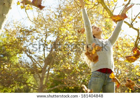 Woman Throwing Autumn Leaves In The Air - stock photo