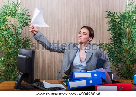 Woman throwing papers in the office under stress - stock photo