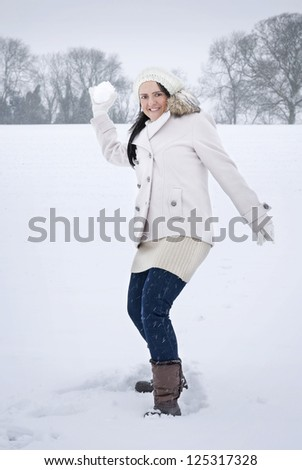 woman throwing snowball in snow covered field - stock photo