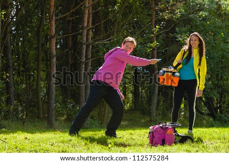 Woman throws a disc, friend waiting on background - stock photo