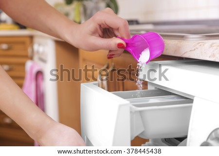 Woman throws laundry detergent into the washing machine close-up. - stock photo