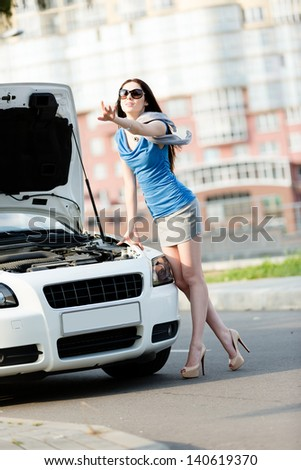 Woman thumbing a lift near the opened hood of the broken cabriolet and waiting for assistance - stock photo