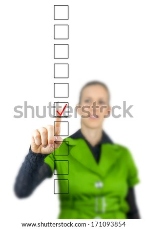 Woman ticking a check box in a vertical line of empty boxes in a survey or questionnaire on a virtual screen or interface with her finger - stock photo