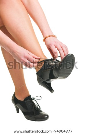 Woman tie her shoes, white isolated background.