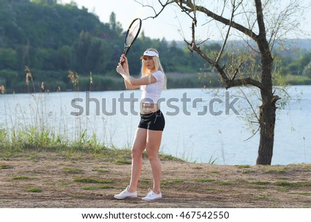 woman to play tennnis, keep right racket and beat the ball to the nature of the street.