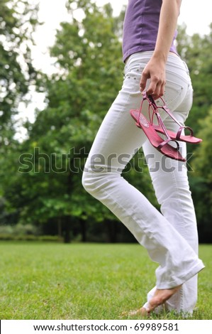 Woman (torso) walking barefoot on grass in park and holding her shoes in hand