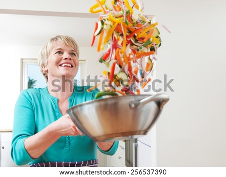 Woman Tossing Vegetables In Wok Whilst Cooking - stock photo