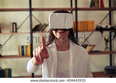 Woman touch something using modern white virtual reality headset glasses
