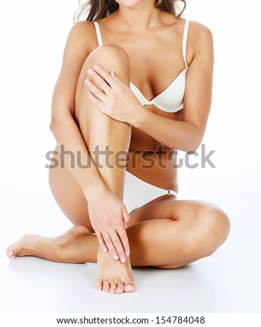 Woman touches her leg  - stock photo