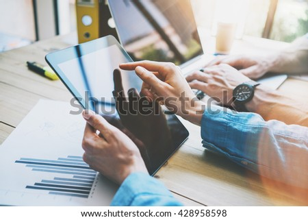 Woman Touching Digital Tablet Hand.Reflections Screen.Project Producers Researching Process.Young Business Crew Working with New Startup Studio. Blurred,film effect. Horizontal closeup photo