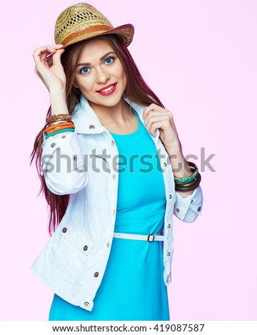 Woman touching hat. Fashion style positive emotion portrait. Isolated on pink background.