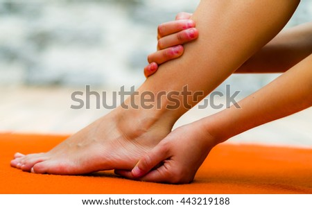 Woman touching her clean foot, one hand in a heel and other in her leg, background of orange color