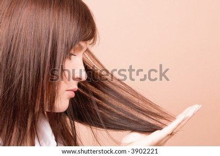 Woman touching her hair isolated on beige background