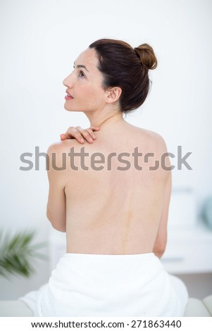 Woman touching her shoulder in medical office - stock photo