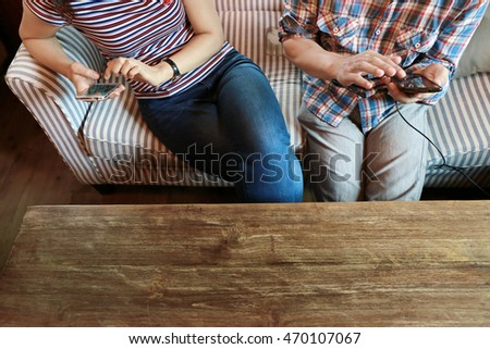 woman touching phone screen and man typing laptop on wood table, internet of things.Couple people working on laptop while discussion and shopping online together, relationship at home.