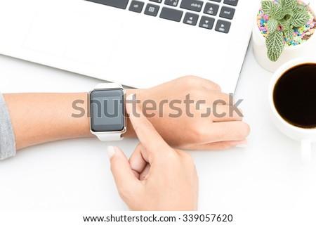 woman touching smart watch hand on work desk - stock photo