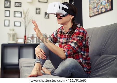 Woman touching something using virtual reality headset glasses and sitting on the couch - stock photo