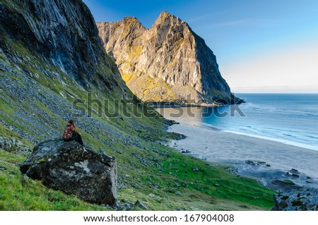 Woman tourist amazed by the view at famous Kvalvika beach hidden between steep cliffs of Lofoten mountains, Norway, sunrise, - stock photo