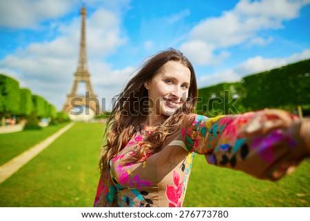 Woman tourist at Eiffel Tower smiling and making travel selfie. Beautiful European girl enjoying vacation in Paris, France - stock photo