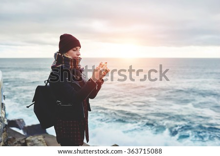 Woman tourist dressed in stylish clothes shoots video of beautiful sea landscape on cell telephone, hipster girl taking photo with mobile phone camera while standing near ocean in cool spring day - stock photo