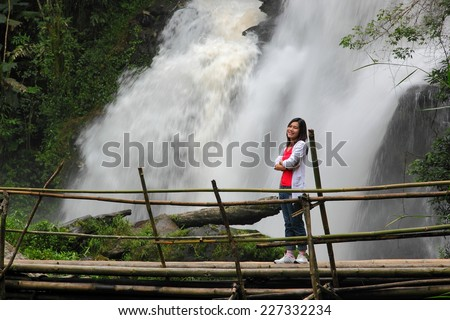 Woman tourist excited by Lak Jung waterfall during travel in Chiang Mai, thailand. - stock photo