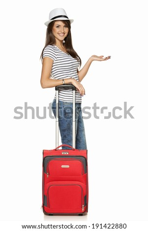 Woman tourist. Full length happy young woman standing with suitcase and showing blank copy space, isolated on white background - stock photo