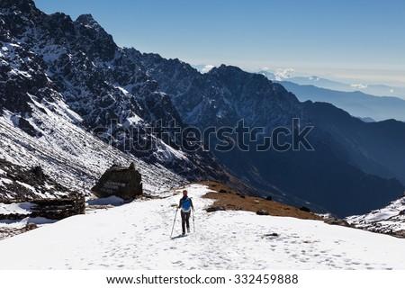 Woman tourist hiking descending snow mountain ridge back view. Gosaikunda trekking route, Langtang mountains region, Nepal - stock photo