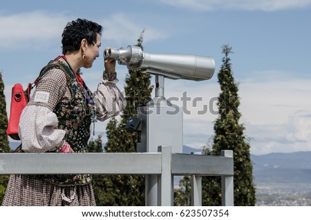Woman tourist look at the sights from above in the telescope.