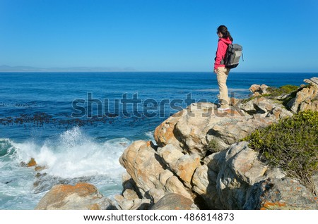 Woman tourist looking at beautiful ocean view in Hermanus, vacation and travel in South Africa