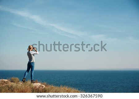 Woman tourist looking through binoculars at distant sea, enjoying landscape - stock photo