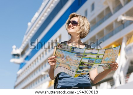 Woman tourist on shore with a map, standing in front of big cruise liner, summer day - stock photo