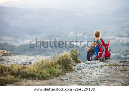 Woman tourist sitting on edge of rock and looking at valley below - stock photo