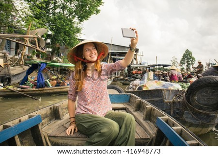 Woman tourist take selfie photo from the boat on Cai Rang floating market, Can Tho, Vietnam