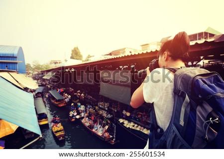 woman tourist taking photo at Damonen Saduak floating market   - stock photo