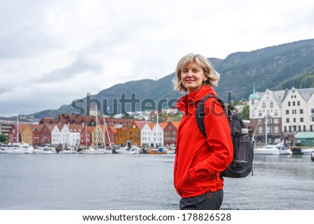 Woman tourist with backpack standing smiling against cityscape of Bergen, Norway, in a summer overcast day - stock photo
