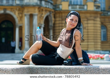 woman tourist with camera and bottle of water relaxing - stock photo