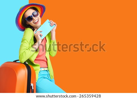 Woman tourist with travel suitcase and blue boarding pass, isolated on summer background - stock photo