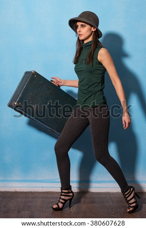 Woman tourist with travel suitcase isolated on blue background