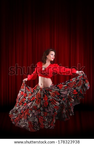 Woman traditional dancer wearing red dress on the dark red stage background - stock photo