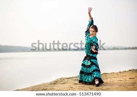 Woman traditional Spanish Flamenco dancer dancing in red dress on the beach